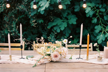 Styled outdoor wedding table with pastel flowers and candles