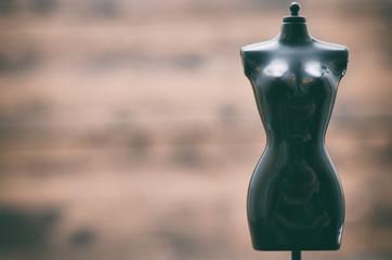 Black female vintage Mannequin stand on a wooden background, fashion design concept