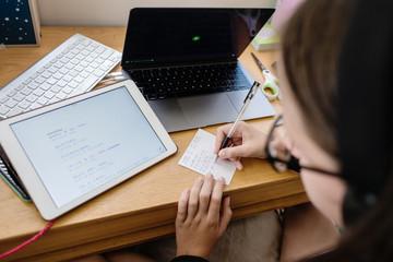 teen doing homework at her desk
