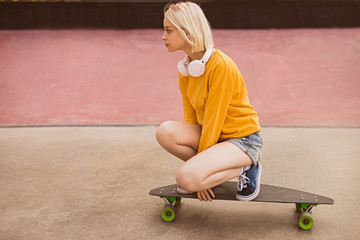 Teen girl riding skateboard on street