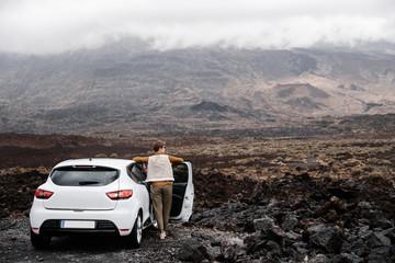 Woman leaning on car, enjoying of mountains beauty. Fototapete