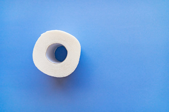 A roll of white toilet paper isolated on a blue background close-up.