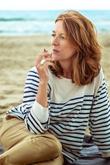 Portrait of a attractive woman of fifty years smoking at the beach