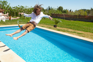 Excited man falling in pool on summer party