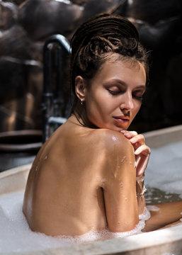 Attractive unusual girl takes a hot bath. Beautiful bathroom with large stone bath