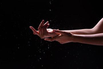 Crop hands of woman under splashing water