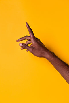 Black man raising index finger against yellow background