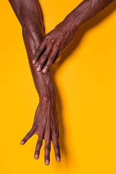 Black man touching his forearm with hand on yellow background