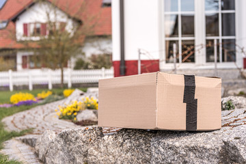 Parcel from a postal delivery is left in the garden because the recipient is not at home.