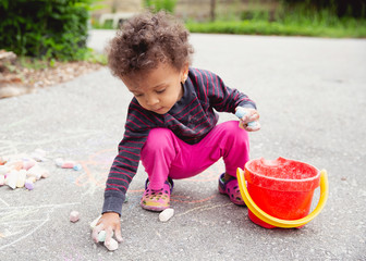 Cute toddler child picking up her pieces of chalk after drawing on the asphalt driveway