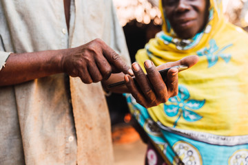 Hands of older man holding a cellphone and a blurred african muslim woman background