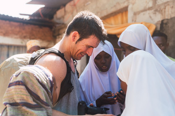 Traveller man showing the pictures to a zanzibari young women