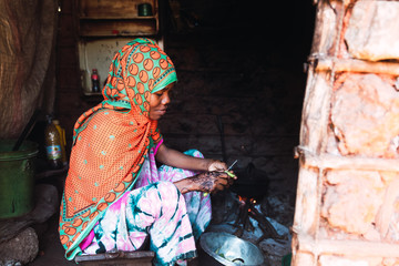 Young woman cooking on the floor of a humble house