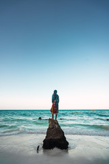 silhouette of a woman with her back on a log trunk facing the turquoise water beach