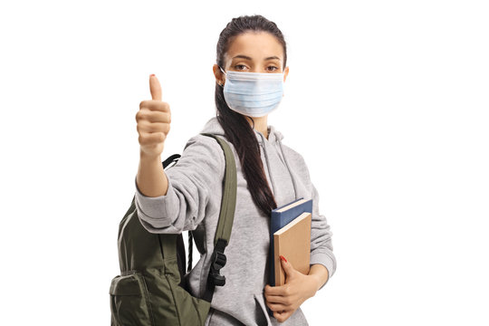Female student with a medical face mask showing thumbs up