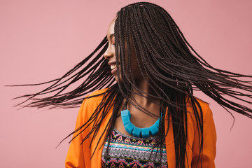 Portrait Of Beautiful Smiling African-American Woman With Bradis On Pink Background