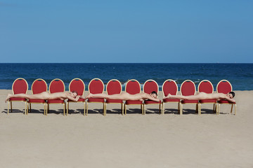 Portrait of naked women lying on theater chairs on beach