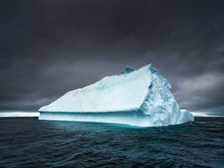 long blue iceberg under dramatic sky in Antarctica