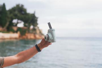 Male hand holding a polaroid camera