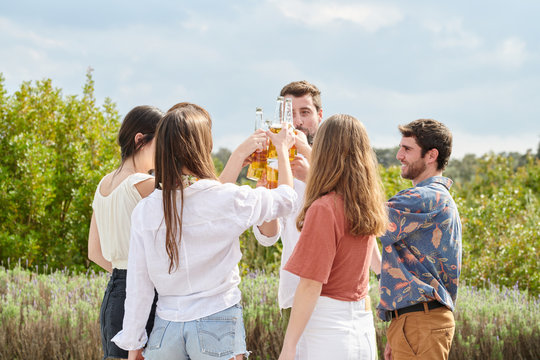 Content young people clinking with bottles of beer