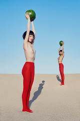Portrait of women standing with watermelons on beach