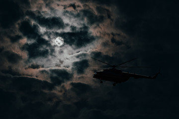 Poster Helicopter Silhouette of a military helicopter flying on a moonlit night against a cloudy dark sky