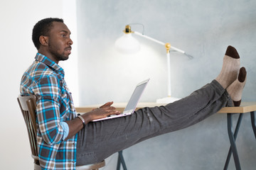 Handsome Afro American businessman in casual clothes with laptop