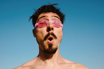 Man in swimming goggles summer vibrant portrait
