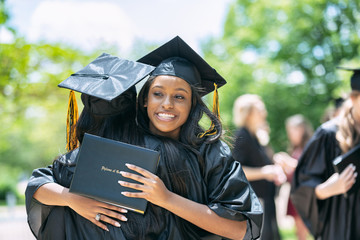 Young women embracing each other after graduation ceremony on campus