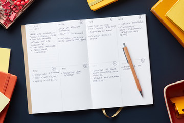Planner with notes on blue desk