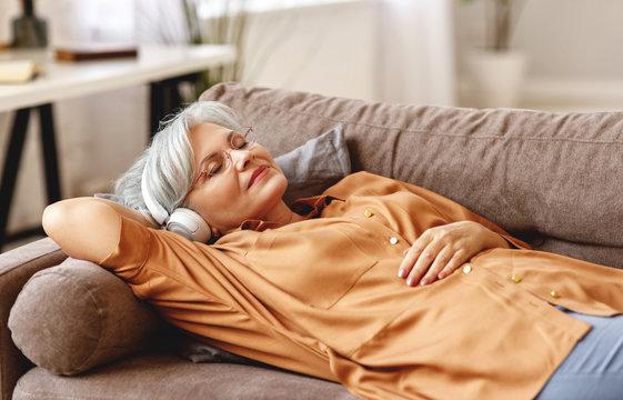 Senior woman listening to music lying on sofa