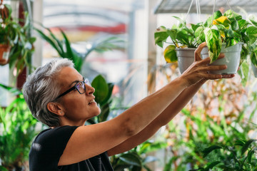 Mid adult woman placing flower pots in the garden
