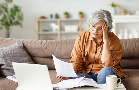 Stressed senior freelancer reading document