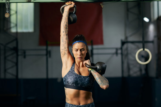 Brunette woman workout with kettlebells.