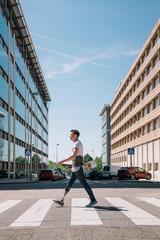Skater with prosthetic leg crossing street in city