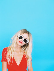 Happy Blonde woman in red dress against blue background