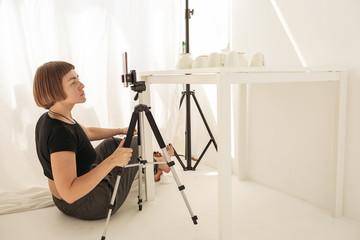 Woman take photos with porcelain via smartphone