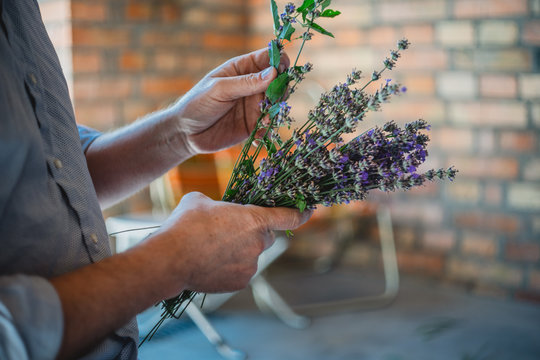 Man holds lavender and ties it to bouquet