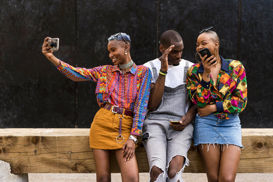 Mobile phone addiction. Afro friends using mobile phone.