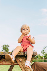 Girl sitting on wooden table in park