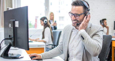 Confident male customer support operator with headset working in call center Fototapete
