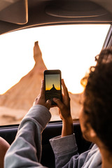 Woman taking a photo of Castil de Tierra, which is a geology formation in spain. lo