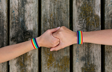 Unrecognizable persons holding hands with gay flag bracelets over an aged wooden table