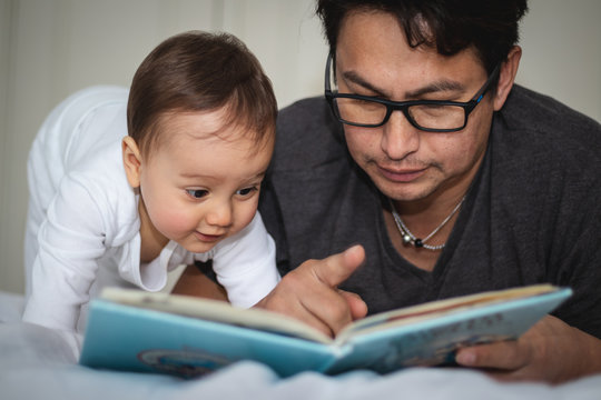 Baby and daddy reading book on the bed