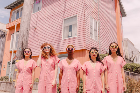 Women in pink jumpsuits standing outdoors