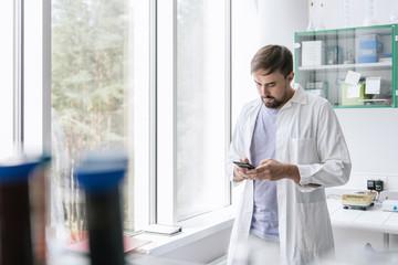 Man in lab using phone