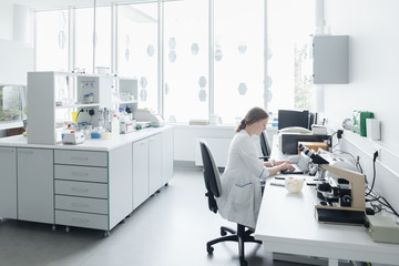 Woman sitting at computer in laboratory