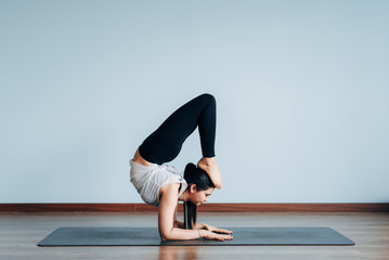 Pretty sporty Indian woman doing difficult yoga pose