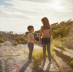 Sister and brother holding hands looking out over a scenic landscape