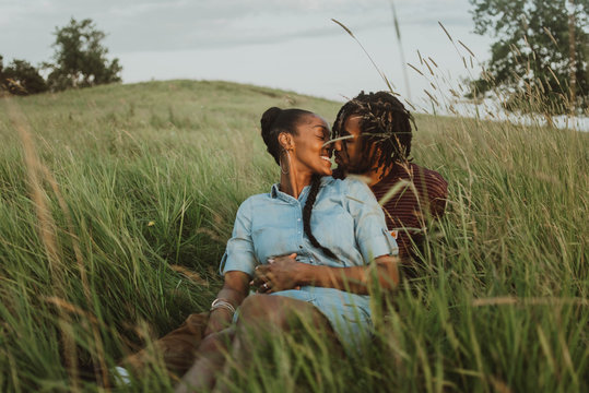 A young engaged African American couple posing for pictures in a field at sunset